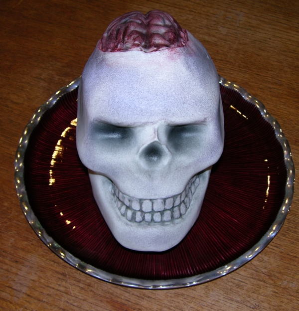 completed skull cake with a brain sticking out of the top