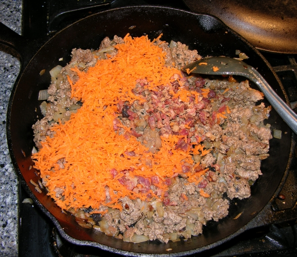 adding carrot, bacon, and garlic to pan