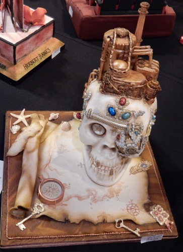 A steampunk skull and map, very nicely done.  Baker unknown.