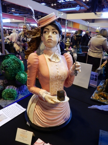 life size cake of lady eating cake